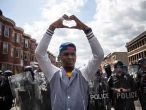 A man makes a heart shape with his hands during a protest near the CVS pharmacy that was set on fire yesterday during rioting after the funeral of Freddie Gray, on April 28, 2015 in Baltimore, Maryland. (Photo: Andrew Burton/Getty Images)