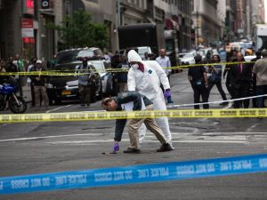 NEW YORK, NY - MAY 13: Crime scene investigators inspect a hammer used in an attack on a police officer on May 13, 2015 in New York City. The attacker was shot twice by a police officer and is currently in the hospital undergoing medical treatment. (Photo by Andrew Burton/Getty Images)