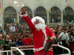 BETHLEHEM: A Palestinian Santa Claus throws confetti, December 24, 1993, to one of the largest crowds ever to watch the Latin Christmas procession since the start of the Intifada in 1987. (SVEN NACKSTRAND/AFP/Getty Images)