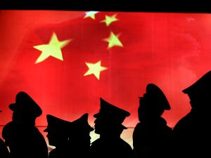 BEIJING, CHINA - MARCH 1: (CHINA OUT) Security guard walk past the Chinese national flag at the Military Museum of Chinese People's Revolution on March 1, 2008 in Beijing, China. From March 1, the Military Museum of Chinese People's Revolution becomes the first national level museum which opens to the public for free in Beijing. (Photo by China Photos/Getty Images)