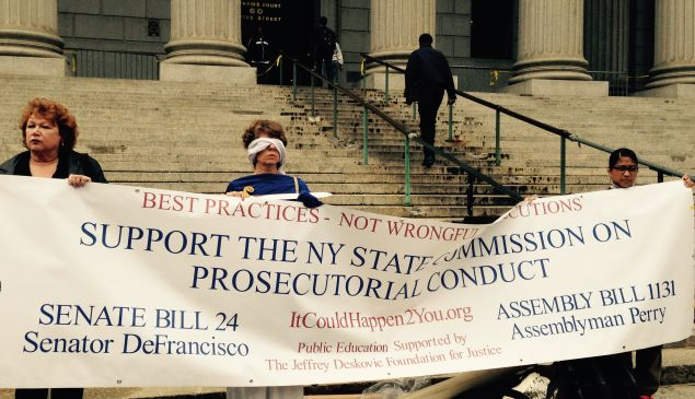 Protesters, one dressed as Lady Justice, push for a State Commission on Prosecutorial Conduct (Photo: Will Bredderman).