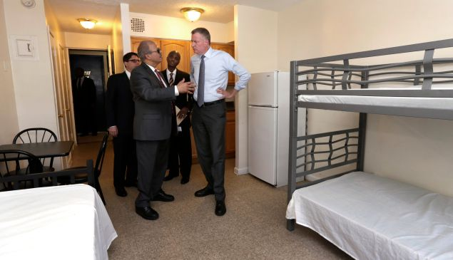 NEW YORK, NY - MAY 11: New York Mayor Bill de Blasio, right, listens to Acacia Network CEO Raul Russ, foreground left, as he visits a room at the Corona Family Residence, a homeless facility, May 11, 2015 in the Queens borough of New York City. Mayor deBlasio made an announcement on his effort to combat the city's homelessness crisis. Also in the visit are Dept. of Investigations Commissioner Mark Peters, background left, and Dept. of Homeless Services Commissioner Gilbert Taylor.