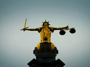 LONDON - DECEMBER 12: A statue of the scales of justice stands high above the Old Bailey on December 12, 2003 in London. Ian Huntley is accused of murdering youngsters Jessica Chapman and Holly Wells, his ex-girlfriend Maxine Carr is accused of conspiring to pervert the course of justice. (Photo by Ian Waldie/Getty Images)
