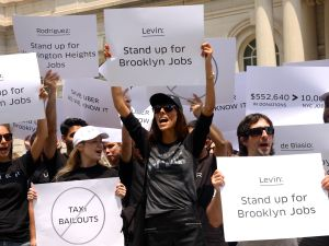 Uber drivers and supporters stood on the steps of City Hall on Tuesday afternoon, protesting a proposed bill that could severely limit the number of Uber cars on the road over the next year. (Giulia Olsson/The New York Observer)