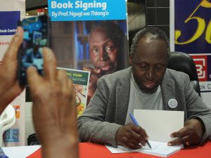 "Internationally celebrated author, playwright and critic, Kenyan Ngugi wa Thiong'o is photographed by a fan using a mobile phone on June 13, 2015 during a book signing to celebrate the golden jubilee of his first book 'Weep Not Child' in the Kenyan capital, Nairobi. A 2014 nominee for the Nobel Prize for literature, Ngugi's 50 year literary career, fraught with dangers, has seen him jailed and therafter forced into exile by successive regimes of the time and his latest visit is seen as a real homecoming after he was received at State House by current President Uhuru Kenyatta who's father, Kenya's powerful first President Jomo Kenyatta jailed Ngugi without trial in 1977 over his critical play Ngaahika Ndeeda, (I will Marry When I Want), before being forced into exile after his release during Kenyatta's successor, President Daniel Arap Moi's rule. ""This is not the Kenya of yesterday but a Kenya that needs all your talents. It is time for you to come back and help us build the country,"" Kenyatta is quoted as saying in the local press. AFP PHOTO/Tony KARUMBA"