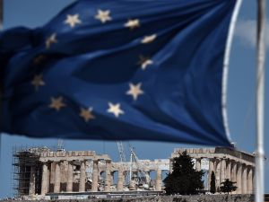 An EU flag waves above the ancient temple of Parthenon atop the Acropolis hill in Athens on July 7, 2015 (Photo: Aris Messinis/AFP/Getty Images).