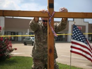 CHATTANOOGA, TN - JULY 18: Ronald May prays as he supports a cross at a memorial setup in front of the Armed Forces Career Center/National Guard Recruitment Office which had been shot up on July 18, 2015 in Chattanooga, Tennessee. According to reports, Mohammod Youssuf Abdulazeez, 24, opened fire on the military recruiting station on July 16th at the strip mall and then drove to an operational support center operated by the U.S. Navy and killed four United States Marines there and a Navy sailor. (Photo by Joe Raedle/Getty Images)