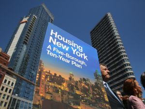 A sign for New York City Mayor Bill de Blasio's new housing plan stands at an affordable housing construction site.
