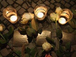 BERLIN, GERMANY - NOVEMBER 09: Candles placed at Stolpersteine by local people commemorating the 75th anniversary of the Kristallnacht pogroms cast light on the names of Jewish residents murdered in the Holocaust on November 9, 2013 in Berlin, Germany. Stolpersteine are concrete cobblestones afixed with brass plaques that memorialize local Jewish residents who were murdered or expelled by the Nazis. Events are taking place across Germany today and tomorrow to commemorate the day in 1938 when Nazi gangs across Germany and Austria burned down over 1,000 synagogues, smashed Jewish-owned businesses, looted Jewish residences and killed several hundred Jews. Anti-Semitism was a central component of Adolf Hitler's rise to power and won him wide-spread sympathy among ordinary Germans and Austrians. (Photo by Sean Gallup/Getty Images)