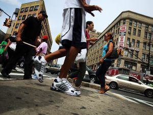 NEW YORK, NY - AUGUST 06: People walk in an area of the Bronx which is the center of the outbreak Legionnaires disease on August 6, 2015 in New York City. It is believed that cooling towers in the area contributed to the illness which is believed to be contracted by inhaling mists from contaminated bacteria in the water source. The Bronx, and specifically the area around the Opera Hotel on East 149th Street, is in the middle of the largest outbreak of Legionnaires disease in New York City's history. New York authorities announced that as of Wednesday night the illness has now sickened nearly 100 people since July 10, with at least eight people having died. (Photo by Spencer Platt/Getty Images)