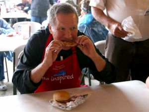 Republican presidential candidate and Ohio Gov. John Kasich eats a pork chop while visiting the Iowa Pork Producers Pork Tent during the Iowa State Fair on August 18, 2015 in Des Moines, Iowa. (Justin Sullivan/Getty Images)