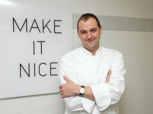 Chef Daniel Humm at Eleven Madison Park, standing next to a poster with the restaurant's slogan. (Photo: Getty Images)
