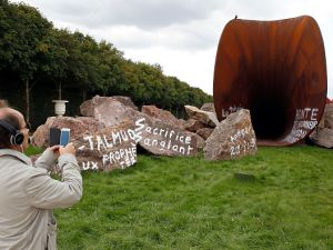 """A visitor takes a picture of """"Dirty Corner"""" by artist Anish Kapoor, vandalized for the second time in the gardens of the Chateau de Versailles. (Photo by Chesnot/Getty Images)"""