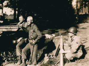 "EH3749P 18 September 1944 Ernest Hemingway stands in uniform beside Colonel Charles ""Buck"" Lanham, in Schweitzer Germany, WWII. An unidentified soldier kneels to hold ammunition."