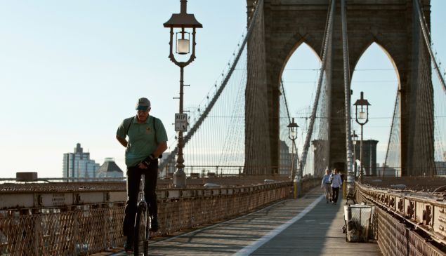 A man rides a unicycle across the Brooklyn Bridge into Manhattan.