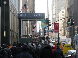 Crowds of bundled up pedestrians walk along 5th Avenue November 21, 2014 in New York. Cold temperatures and high winds made for a cold day of shopping. AFP PHOTO/Don Emmert (Photo credit should read DON EMMERT/AFP/Getty Images)