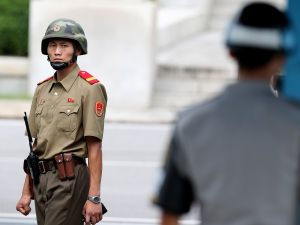 PANMUNJPM, SOUTH KOREA - JULY 27: A North Korean soldiers looks on as South Korean and United Nation officials visit after attending a ceremony to commemorate the 62nd Anniversary of the Korean War armistice agreement at Panmunjom on July 27, 2015, South Korea. On June 25, 1950, soldiers of the North Korean army breached the 38th parallel invading the Republic of South Korea, marking the beginning of the Korean War. On July 27 1953, a signed armistice agreement brought the three-year conflict to an end. (Photo by Jeon Heon-Kyun-Pool/Getty Images)