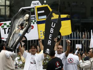 Taxi drivers demonstrate outside the chamber of deputies in the neighborhood of Se, Sao Paulo, Brazil, on September 9, 2015, against the use of the Uber application in the country. The demonstration was called by the Brazilian association of taxi unions. AFP PHOTO / Miguel SCHINCARIOL (Photo credit should read Miguel Schincariol/AFP/Getty Images)