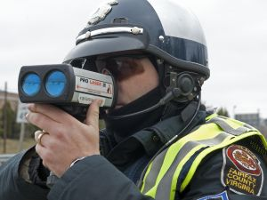 A Fairfax, Virginia, motorcycle Officer aims his ProLaser III, Lidar, towards drivers that may be speeding March 10, 2009, on Lee Highway-Route 29. AFP Photo/Paul J. Richards