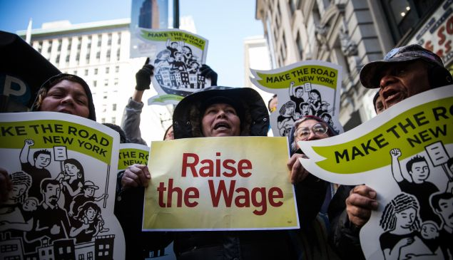 """NEW YORK, NY - MARCH 18: Women hold banners during a protest for higher wages for fast food workers on March 18, 2014 in New York City. The protest, arranged by the group """"Fast Food Forward"""" accused fast food corporations of corporate greed and withholding wages. (Photo by Andrew Burton/Getty Images)"""