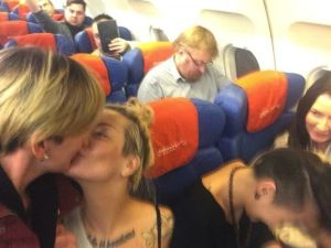 Lesbian activists who happened to be on a plane with anti-gay Russian lawmaker Vitaly Milonov arranged for him to photobomb them while kissing.