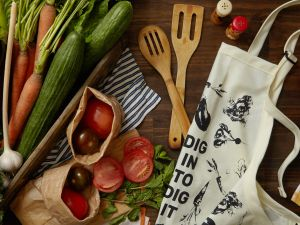 "The Food for Thought, Food for Life collection features an apron that reads ""Dig in to Dig it."""