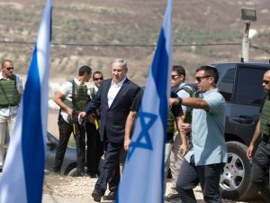Israeli Prime Minister Benjamin Netanyahu (C) walks at the Horon army camp near the Palestinian city of Nablus in the Israeli-occupied West Bank, on October 6, 2015. Israel demolished the homes of two Palestinians behind attacks and sealed off a room in another, the army said, after Netanyahu pledged an iron fist against mounting unrest. AFP PHOTO / MENAHEM KAHANA (Photo credit should read MENAHEM KAHANA/AFP/Getty Images)
