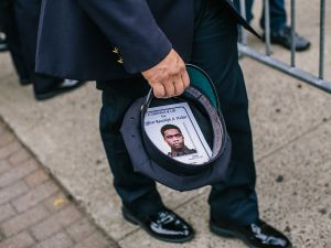 A police officer keeps Randolph Holder's funeral announcement in his hat (Photo by Christopher Gregory/Getty Images).