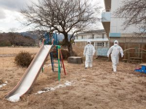 NAMIE, FUKUSHIMA PREFECTURE - FEBRUARY 27: Police sergeant Yabuki Koshin and Constable Kanno Tomoyasu walk the grounds of Obori Kindergarten whilst on patrol within the 20km exclusion zone around Fukushima Daiichi nuclear plant, on February 27, 2012 in Namie, Fukushima prefecture, Japan. Police patrol the evacuated 20km exclusion zone, which is in force around the stricken Fukushima Daiichi nuclear plant, and which encompasses six towns and two villages, looking for any signs of burglaries or crime in the now uninhabited zone. The exclusion zone used to be home to approximately 73,000 people but all have been evacuated by the government and are now restricted from returning home due to high levels of radioactive contamination from the explosions at the TEPCO owned Fukushima Daiichi nuclear plant following the earthquake and tsunami of March 11 2011. (Photo by Jeremy Sutton-Hibbert/Getty Images)