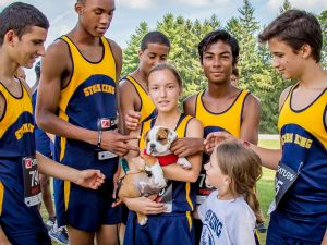 Members of the Storm King School's track team with Winston, one of the five dogs on campus.