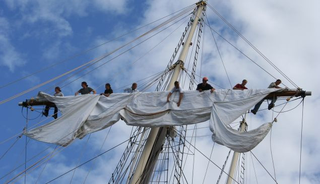 A crew unfurls the mast aboard Peacemaker.