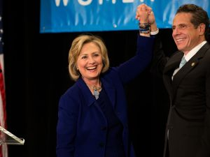 Former U.S. Secretary of State and U.S. Sen. Hillary Rodham Clinton raises the hand of New York Gov. Andrew Cuomo at a Cuomo campaign event in 2014. (Photo by Bryan Thomas/Getty Images)