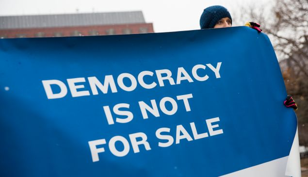 WASHINGTON, DC - JANUARY 21: An attendee holds a sign during a rally calling for an end to corporate money in politics and to mark the fifth anniversary of the Supreme Court's Citizens United decision, at Lafayette Square near the White House, January 21, 2015 in Washington, DC. Wednesday is the fifth anniversary of the landmark ruling, which paved the way for additional campaign money from corporations, unions and other interests and prevented the government from setting limits on corporate political spending. (Photo by Drew Angerer/Getty Images)
