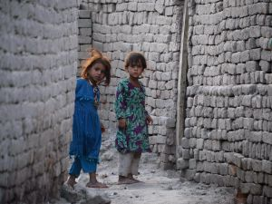In this photograph taken on July 5, 2015, Afghan girls who fled from Kot district of the eastern Nangarhar' province, following threats from the Islamic State group to leave their homes, look around a corner next to their temporary homes in Jalalabad. Authorities said more than 250 families had moved from Kot district of the eastern province to Jalalabad, with representatives of the displaced families telling AFP that Islamic State fighters had ordered families whose members were working for the government or Afghan National Security Forces to leave their homes. AFP PHOTO / Noorullah Shirzada (Photo credit should read Noorullah Shirzada/AFP/Getty Images)