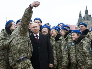 Russian President Vladimir Putin (C) poses for a selfie with young activists at the Red Square in Moscow on November 4, 2015 during celebrations for National Unity Day marking the 403rd anniversary of the 1612 expulsion of Polish occupation forces from the Kremlin. AFP PHOTO / POOL / NATALIA KOLESNIKOVA (Photo credit should read NATALIA KOLESNIKOVA/AFP/Getty Images)