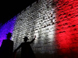 Israeli Jews walk past Jerusalem's Old City Ottoman Walls illuminated in red, white and blue, the colors of the French flag, in Jerusalem on November 15, 2015 in solidarity with France and the attacks in Paris. (GALI TIBBON/AFP/Getty Images)