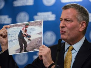 New York City Mayor Bill de Blasio holds up a photo of a the body of a dead child refugee being recovered from a beach (Photo: Andrew Burton for Getty Images)