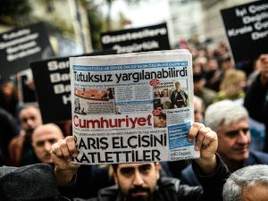 """Members of journalism unions shout slogans and hold placards """"reading: Freedom for journalist"""" on November 29, 2015 in Istanbul, during a demonstration after the arrest of their Editor in Chief. A court in Istanbul charged two journalists from the opposition Cumhuriyet newspaper with spying after they alleged Turkey's secret services had sent arms to Islamist rebels in Syria, Turkish media reported. Editor-in-chief Can Dundar and Erdem Gul, the paper's Ankara bureau chief, are accused of spying and """"divulging state secrets"""". Both men were placed in pre-trial detention. AFP PHOTO/OZAN KOSE / AFP / OZAN KOSE (Photo credit should read OZAN KOSE/AFP/Getty Images)"""