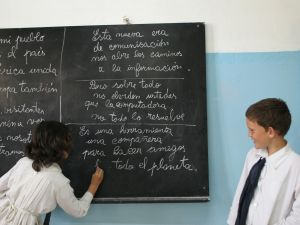 "TO GO WITH AFP STORY A schoolgirl writes old-fashion with chalk on a blackboard while in class 07 December, 2007 in Villa Cardal, 80km from Montevideo. The sentences written on the board aim to explain basic concepts and advantages of the use of computers in education: ""This new communication era opens the way to information"", ""But above all, don't forget that computers can't solve it all"" and ""It is a tool, a companion to make friends around the planet"". The small 2,000 inhabitants village of Villa Cardal was chosen by its peculiar characteristics to host the first stage of the ""Ceibal"" (A native forest of 'ceibo' trees) project, consisting in assigning a specially designed laptop to each schoolboy to be used as a learning tool and to connect the young students of even remote places to the rest of the world. AFP PHOTO PANTA ASTIAZARAN (Photo credit should read PANTA ASTIAZARAN/AFP/Getty Images)"