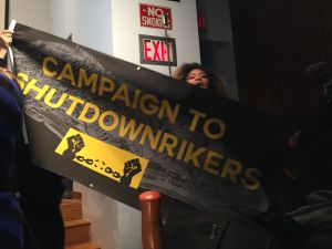 A woman holds up a banner calling for Rikers Island to be shut down.