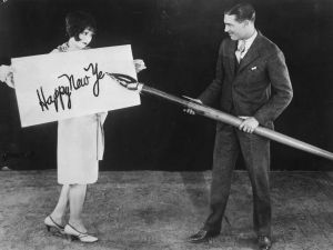 circa 1925: American actress Clara Bow (1905 - 1965) holds up a large card while actor Larry Gray inscribes a New Year's greeting with a giant pen. (Photo by General Photographic Agency/Getty Images)