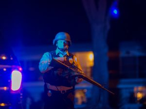 SAN BERNARDINO, CA - DECEMBER 2: A police officer officer guards a police line as officers prepare to raid the home of one or more suspects of a mass shooting at the Inland Regional Center (Photo by David McNew/Getty Images).