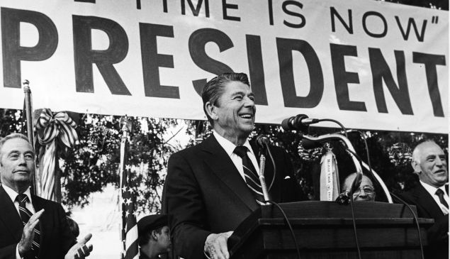 American politician Ronald Reagan smiles as he speaks on his presidential campaign in front of a large banner, 1979. Pennsylvania governor William Scranton (L) applauds. (Photo by Hulton Archive/Getty Images)