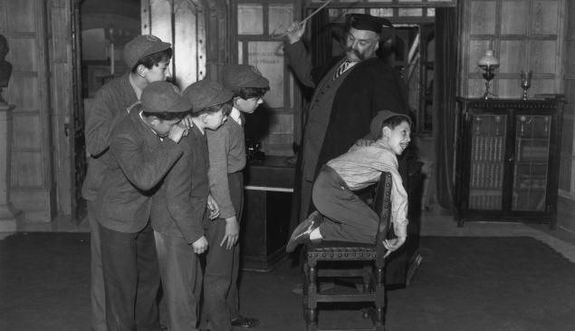 10th November 1959: 'Professor' Jimmy Edwards (1920 - 1988) in rehearsal at Shepherds Bush TV studios is administering a flogging to one of the pupils of 'Chiselbury' school, Paul Norman, watched by his classmates. (Photo by Reg Speller/Fox Photos/Getty Images)