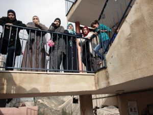 Palestinian women standing on a balcony look at the damaged interior of the home of Bahaa Allyan, a Palestinian who killed three Israelis in a shooting and stabbing attack with an accomplice on a bus in October, after Israeli forces used jackhammers to destroy the walls of the middle floor of a three-story building in the east Jerusalem Palestinian neighbourhood of Jabal Mukaber on January 4, 2016. Allyan, who was shot dead, had on October 13 along with a fellow Palestinian shot and stabbed passengers on a bus in Jerusalem, resulting in the death of two Israelis and a joint US-Israel national. AFP PHOTO / AHMAD GHARABLI / AFP / AHMAD GHARABLI (Photo credit should read AHMAD GHARABLI/AFP/Getty Images)