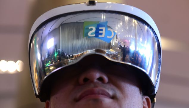 Attendee Wei Rongjie wears a working prototype of his HoloSeer AR/VR all-in-one agumented reality and virtual reality headseat, January 6, 2016 at the CES 2016 Consumer Electronics Show in Las Vegas, Nevada. Wei says the HoloSeer headset has a 100 degree angle of view and is in the second round of Kickstarter funding. AFP PHOTO / ROBYN BECK / AFP / ROBYN BECK (Photo credit should read ROBYN BECK/AFP/Getty Images)