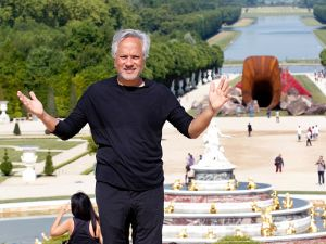 VERSAILLES, FRANCE - JUNE 05: British contemporary artist of Indian origin Anish Kapoor poses in front of his artwork named 'Dirty Corner' at the opening of his exhibition of his works in the gardens of the Chateau de Versailles on June 5, 2015, in Versailles, France. This exhibition takes place from June 9 until November 01, 2015 in the gardens of the 'Chateau de Versailles'.
