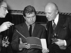 Irish painter Francis Bacon (1909 - 1992) (centre), reading his exhibition catalogue, and English photographer Cecil Beaton at the Marlborough Gallery, London.