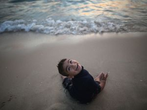 GAZA CITY, GAZA - JUNE 13: A young Palastinian boy laughs as the waves rush towards him on Gaza beach on June 13, 2015 in Gaza City, Gaza. Palestinians are taking the opportunity to relax and enjoy picnics on Gaza beach before the holy month of Ramadan which starts next week. Thousands of Palestinians descend on the 75km sandy beach of Gaza each day to relax, fish and escape the noise and heat of the city. The devastation across Gaza can still be seen nearly one year on from the 2014 conflict between Israel and Palestinian militants. Money pledged by the international community six months ago to rebuild Gaza has not materialised leaving many Palestinians impoverished and still suffering with the poor economy. (Photo by Christopher Furlong/Getty Images)