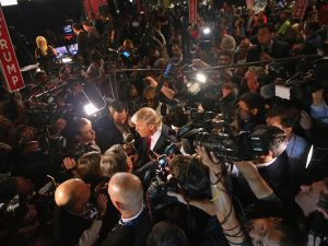 Republican presidential candidate Donald Trump (C) talks to reporters in the 'Spin Alley' after the first prime-time presidential debate hosted by FOX News and Facebook at the Quicken Loans Arena August 6, 2015 in Cleveland, Ohio.